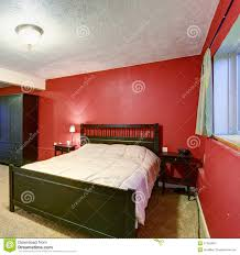 bedroom with red walls black color furniture and beige blanket