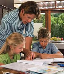 Photo of a father reviewing homework with his two children