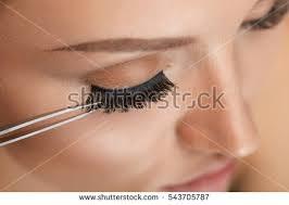 eyelashes beautiful woman applying false eyelashes stock photo