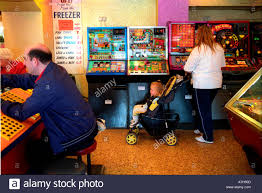 people playing bingo and slot machines in a games arcade stock