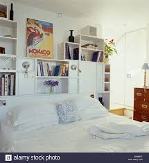 large storage shelves large poster on fitted storage shelves behind bed with white