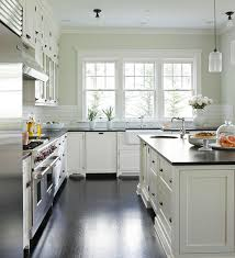 Green And White Kitchen Cabinets Reflective Surfaces And Large Windows Keep The Spacious Black And