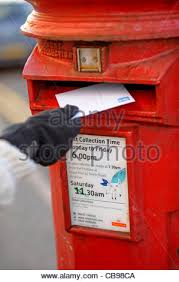 hand posting christmas cards letter in uk post box set in wall