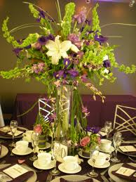 tall cylinder with green purple and white flowersevery bloomin