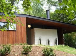 wooden exteriors of mid century mod houses with warm lamp with