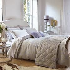 bed pillows brown wooden floor with skin rugs white king size bed white