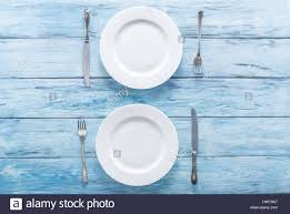 plate table top two white empty plates and cutlery on blue table top view stock