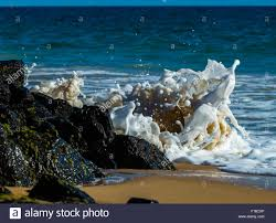 frozen waves gentle waves crashing into rocks causing a beautiful looking scene