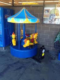miniature carousel ride outside a rite aid kiddie rides