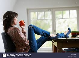 Feet On The Desk Mature Woman With Feet On Desk Drinking Coffee Stock Photo
