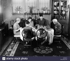1940s extended family sitting around dining room table saying grace