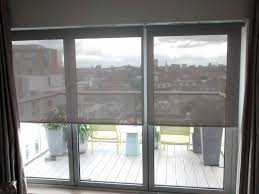 sunscreen roller blinds installed to bifold doors in a penthouse