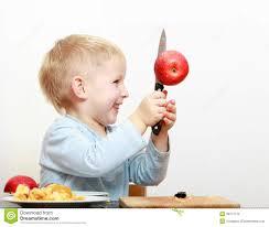 blond boy child kid preschooler with kitchen knife cutting fruit