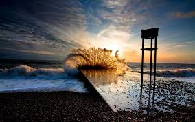oceans mountainous wave breaks sunset clouds sky