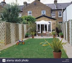 lawn and trellis fence in back garden of townhouse with small