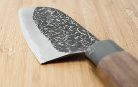 japanese damascus carbon steel knife on wooden plank close up