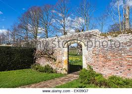 garden gate and arch with old red brick wall and green vine red