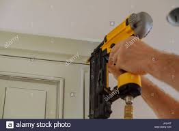 carpenter brad using nail gun to crown moulding on kitchen