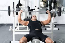 young bodybuilder training in the gym chest barbell incline