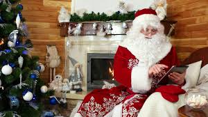 santa claus using gadget saint nicolas sitting in chair with