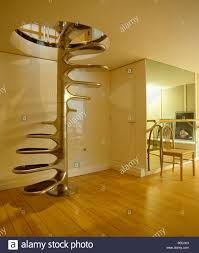stainless steel spiral staircase in modern white hall with wooden