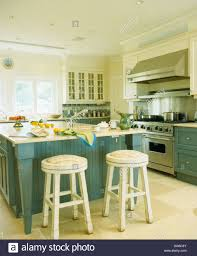 Stools For Island In Kitchen by White Wooden Stools At Breakfast Bar On Island Unit In White