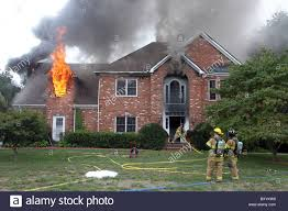 2 stories house fire fighters put out a blaze in a 2 story house stock photo