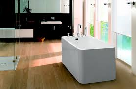 boxes stand alone bathtub with faucet on wooden laminate flooring