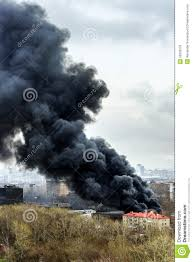 column of black smoke rising above fireplace in the city stock