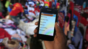 microfinance thesis bill and melinda gates want to fix another messy global problem a man holds up his mobile phone showing a m pesa mobile money transaction page