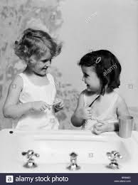 1930 S Bathroom 1930s Two Girls At Bathroom Sink Holding Toothbrush Stock Photo