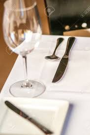 elegant dinner table set with knife fork and wine glass stock
