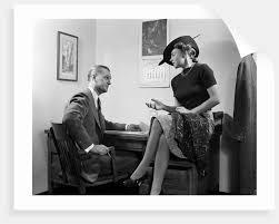 1940s Desk 1940s Woman Sitting On Desk Hat Skirt Hand Gesture Talking