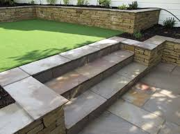 Pea Gravel And Epoxy Patio by This Sloped Garden Has Curved Landscaping With The Slope Held Back