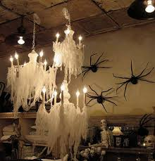 halloween decor cheesecloth over chandelier giant spiders on