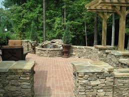 A Manufactured Brick Patio Surrounded With Natural Stone Pillars - Patio wall design