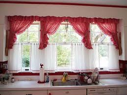pink cafe curtains installed in the kitchen window over the sink