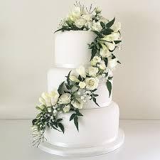 wedding cake greenery white wedding cake with trailing fresh white flowers and greenery