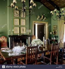 dining room with green walls and wooden furniture stock photo