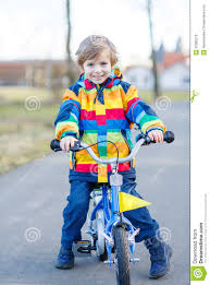 bike raincoat kid boy in safety helmet and colorful raincoat riding bike stock
