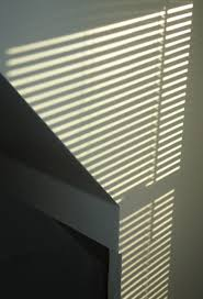 file pattern of light on a white wall made by sun through blinds