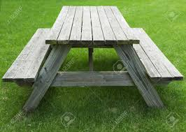 wooden picnic table with benches on a green grass lawn stock photo