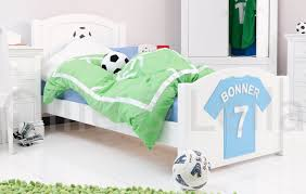 white wooden bed with green bed cover on white floor of modern bedroom white wooden bed with green bed cover on white floor modern look of