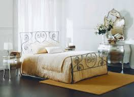 classic bedroom with brown wrought iron bed and brown rug also