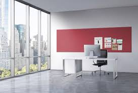 bay window desk wall red cork board wall with black swivel chair and concrete