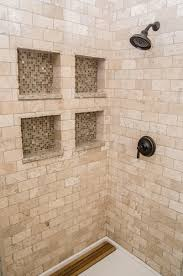 inside the shower with tumbled marble and glass tiled inserts
