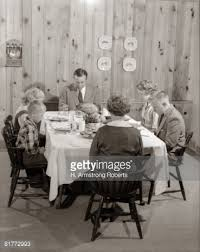 family of 6 seated at dining room table saying grace before