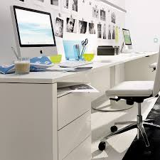 white desk office with few drawers also swivel chairs and computer