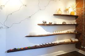 four dark brown wooden floating wall shelves on white wall