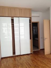 wooden master bedroom closet with white mica slidding doors on